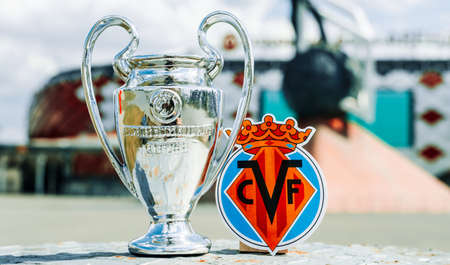 June 14, 2021 Villarreal, Spain. The emblem of the Villarreal CF football club and the UEFA Champions League Cup against the backdrop of a modern stadium.