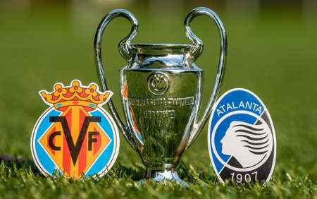 August 27, 2021 Villarreal, Spain. The emblems of football clubs Atalanta BC and Villarreal CF and the UEFA Champions League Cup on the green lawn of the stadium.
