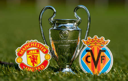 August 27, 2021 Manchester, England. The emblems of football clubs Villarreal CF and Manchester United FC and the UEFA Champions League Cup on the green lawn of the stadium. Editorial