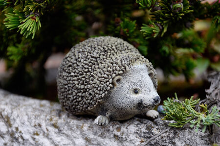 Stone hedgehog sitting as decoration in the garden, in front of a green plants background on the edge of a stone plant pot