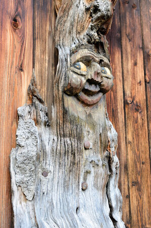burl wood: Carved from a burl wood figure against a dark brown background of wooden boards