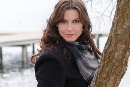 Upper body portrait of a young woman with brown hair and dark green eyes in the fall  winter in front of a lake with a pier in the background and intense eye contact