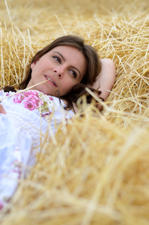 Young, pretty woman with brown hair and dark green eyes lying in the freshly mowed corn field in white dress. summer mood photo