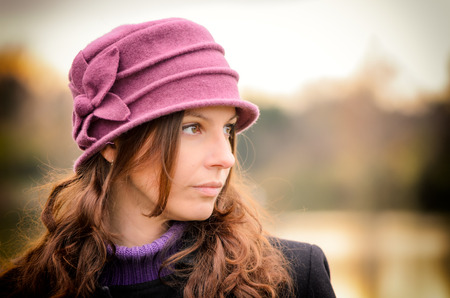 Head Portrait of a pretty young woman with brown hair, dark green eyes and a purple hat in autumn. The view is expectantly into the distance. photo