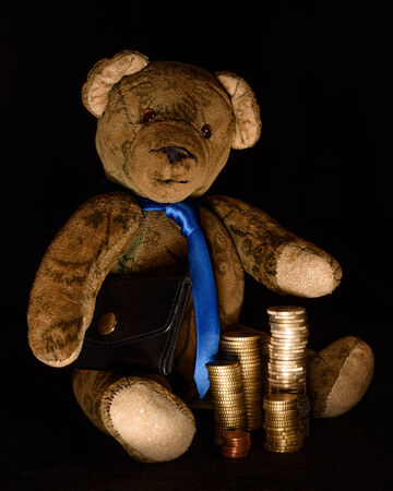 dubious: Teddy as a rogue businessman who makes money transactions hidden in the darkness. He has a black briefcase under his arm and stacked coins in front of him. Studio shot isolated against a black background shown. Stock Photo