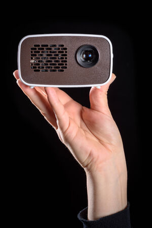 cool gadget: Mini projector held in the hand and isolated against black background