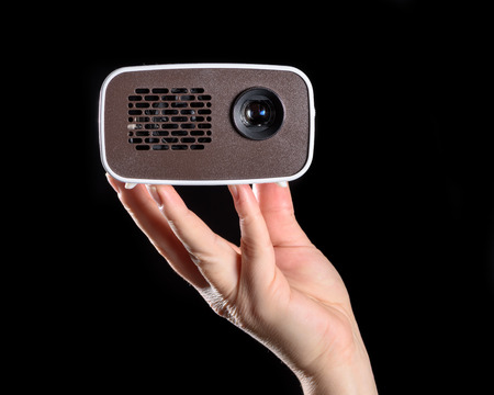 Mini projector held in the hand and isolated against black background