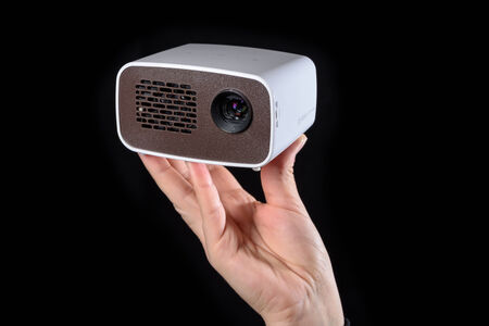 miniaturization: Mini projector held in the hand and isolated against black background