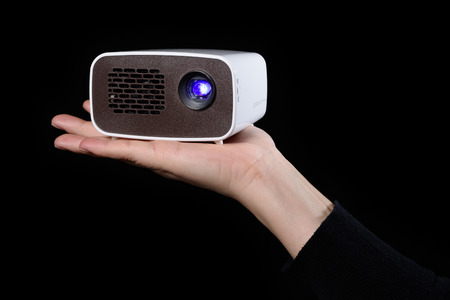 Mini projector held on the palm and isolated against black background