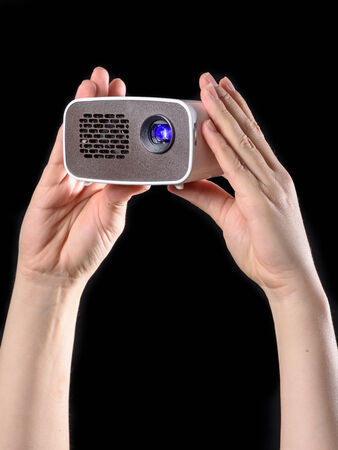 miniaturization: Mini projector presented with two hands and isolated against black background Stock Photo