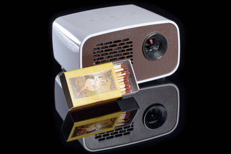 cool gadget: Mini projector with matchbox for size comparison reflecting on a black background Stock Photo