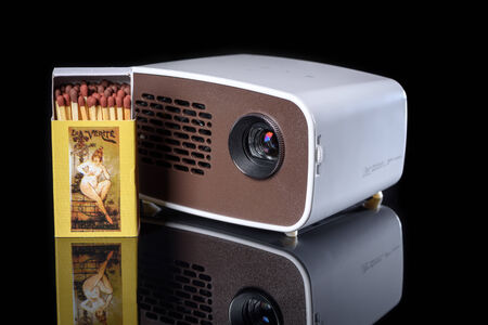 miniaturization: Mini projector with matchbox for size comparison reflecting on a black background Stock Photo