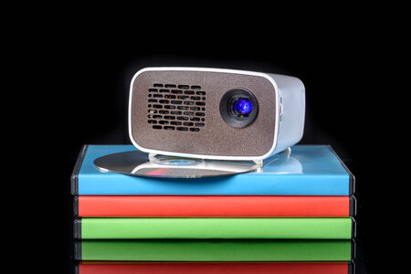 miniaturization: Mini Projector with DVD on DVD cases reflecting on black background