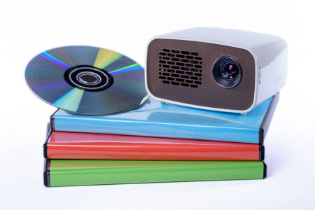 cool gadget: Mini Projector with DVD on DVD cases isolated on white background