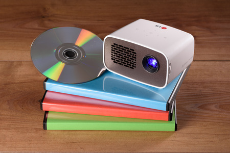miniaturization: Mini Projector with DVD and DVD cases on wooden table Stock Photo