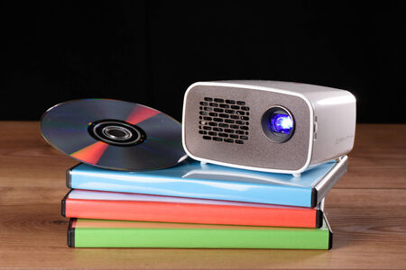 miniaturization: Mini Projector with DVD and DVD cases on wooden table with black background
