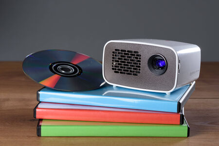 miniaturization: Mini Projector with DVD and DVD cases on wooden table with gray background