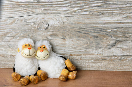 Two sheep lying casually in front of a wooden background and smiling at the viewer