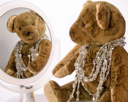 Antique Teddy has adorned herself with jewelry chains and is lookin at herself in the mirror Stock Photo