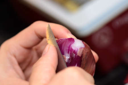 skinning: Hands peeling a onion with a knife