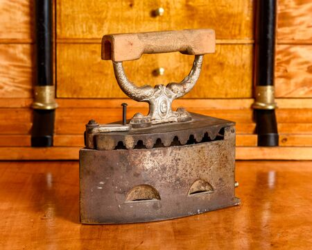 the 19th century: Antique coal iron on antique cherry wood desk, late 19th century Stock Photo