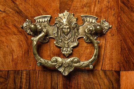 the founder: Antique brass ornament on an old walnut veneer furniture, founder time