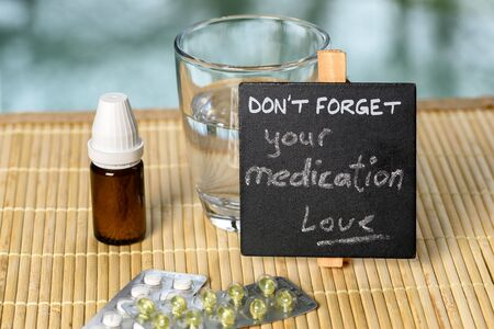 forgetfulness: Medication reminder on bamboo with medicine Stock Photo