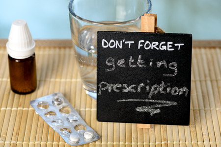 forgetfulness: Prescription reminder on glass table with medicine Stock Photo