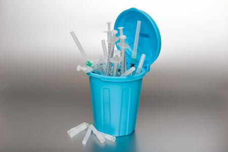 protrude: Blue Garbage can with medical waste. Syringes protrude out of it.
