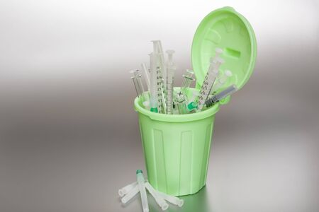 protrude: Green Garbage can with medical waste. Syringes protrude out of it.