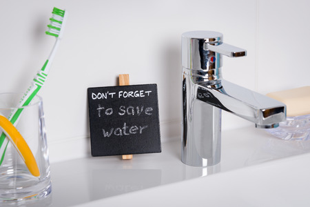 ahorrar agua: Recordatorio para ahorrar agua en el ba�o. Detalle el tiro del lavabo. Foto de archivo