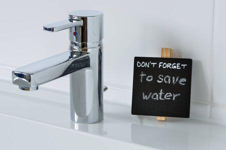 ahorrar agua: Recordatorio para ahorrar agua en el baño. Detalle el tiro del lavabo. Foto de archivo