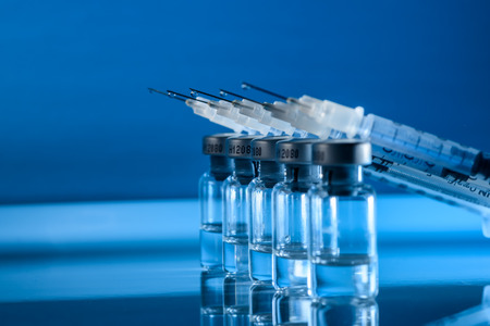 ambient: Battery of syringes in labor, ready for medical research. Blue ambient lighting.