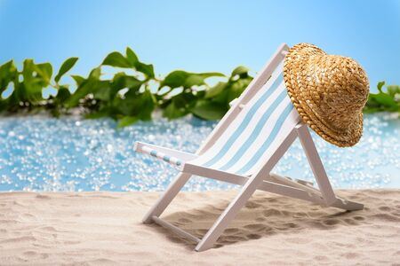 sunhat: Miniature of a sun lounger with sunhat in front of a lagoon symbolizing relaxation at the beach Stock Photo