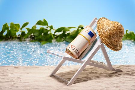 Geld op vakantiepakket van 50 Euro rekeningen die bij het strand op een zonlanterfanter voor een blauwe lagune zitten Stockfoto