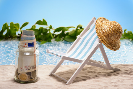 Savings for vacation glass with money bills and coins at the beach Stok Fotoğraf - 40257712