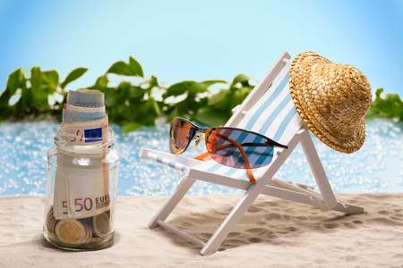 Savings for vacation glass with money bills and coins at the beach