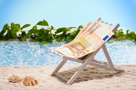 Geld op vakantie pakje van 50 euro biljetten zittend op het strand op een ligstoel in de voorkant van een blauwe lagune