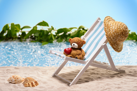 heart under: Warm greetings from holiday miniature of a sun lounger at the beach with little bear on it red heart under its arm