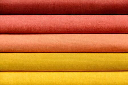 with spines: Stack of Book spines covered with linen for background purpose, red, orange, yellow Stock Photo