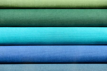 Stack of Book spines covered with linen for background purpose, green and blue Stock Photo