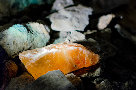 Orange glowing salt crystal in a dark mine (Salzburg, Austria)