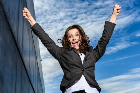 Young Business Woman is jumping for joy in front of blue cloudy sky with office block to the side