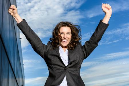 persona saltando: Mujer de negocios joven está saltando de alegría delante de cielo nublado azul con el edificio de oficinas al lado Foto de archivo