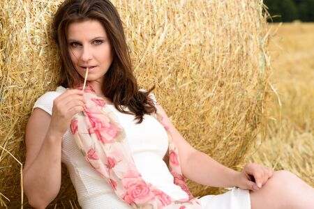 lascivious: Young Caucasian woman with long brown hair is sitting in a fresh mown corn field -  leaning against a bale of straw