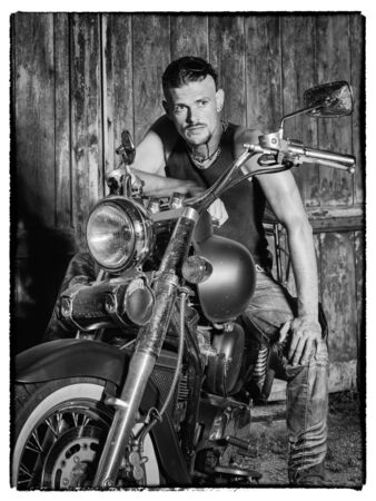 undercut: Tough guy with sparrow beard, undercut and blue jeans sitting on a chopper bike in front of  a green weathered barn door
