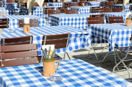 Leerer bayerischer Biergarten mit blauer weißer Tischdecke.