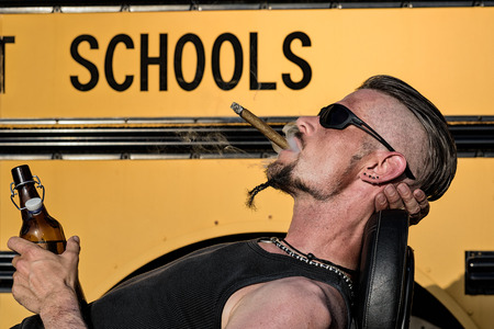 Bad Boys do not like school: Tough guy with sparrow beard, undercut and blue jeans leaning against his chopper motorcycle in front of a yellow, American school bus. He is smoking cigar and drinking beer.