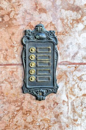 door bell: Old wrought iron door bell sign - without labels on marble stone for background purpose. Stock Photo