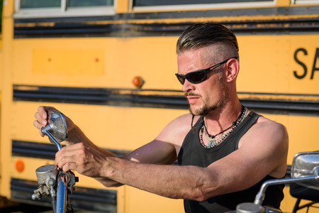 undercut: Tough guy with sparrow beard, undercut, black rip shirt and sun glasses lolling on his chopper motorcycle in front of a yellow, American school bus. Stock Photo